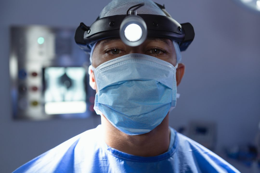 Male surgeon with surgical mask and surgical headlight looking at camera in operation room at hospital
