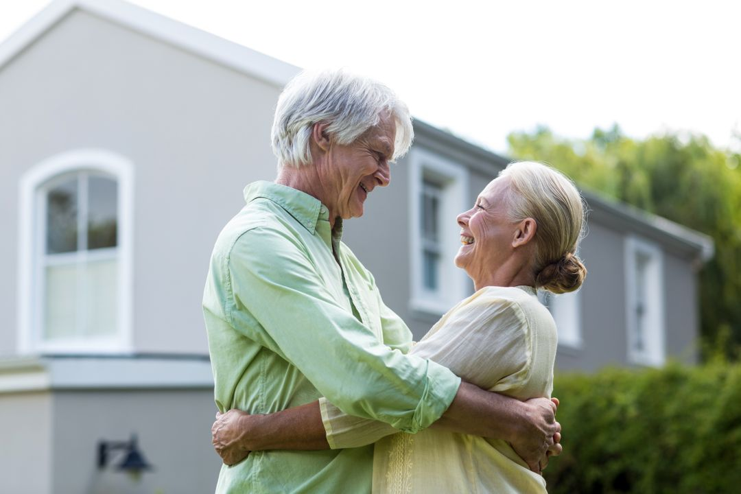 Smiling senior couple embracing in yard against house Free Stock Images from PikWizard