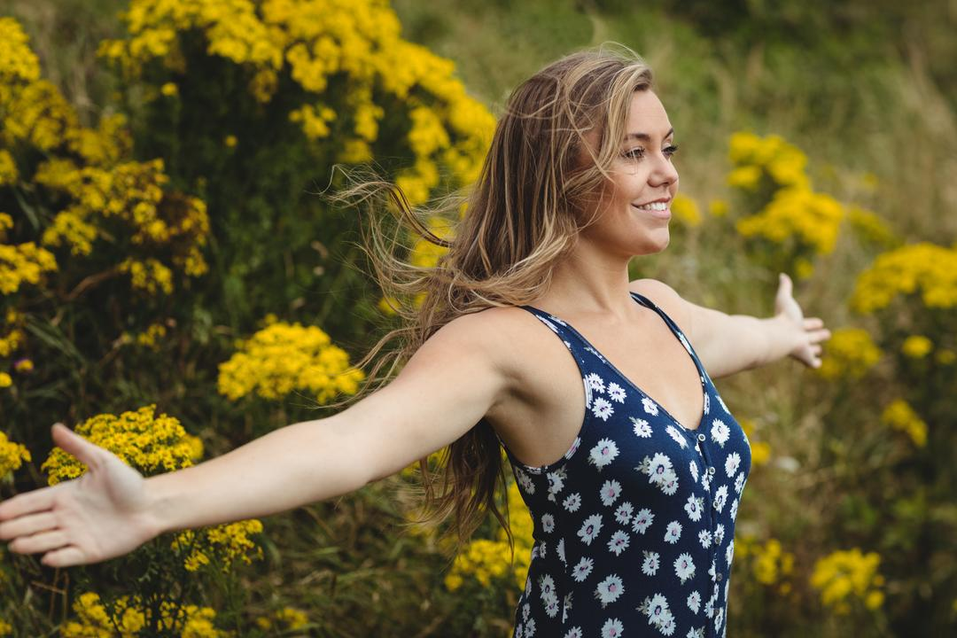 Woman standing with arms outstretched in meadow on a sunny day