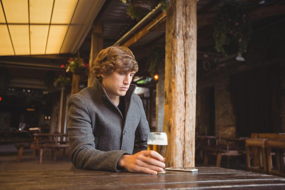 Thoughtful man sitting in bar with glass of beer on table