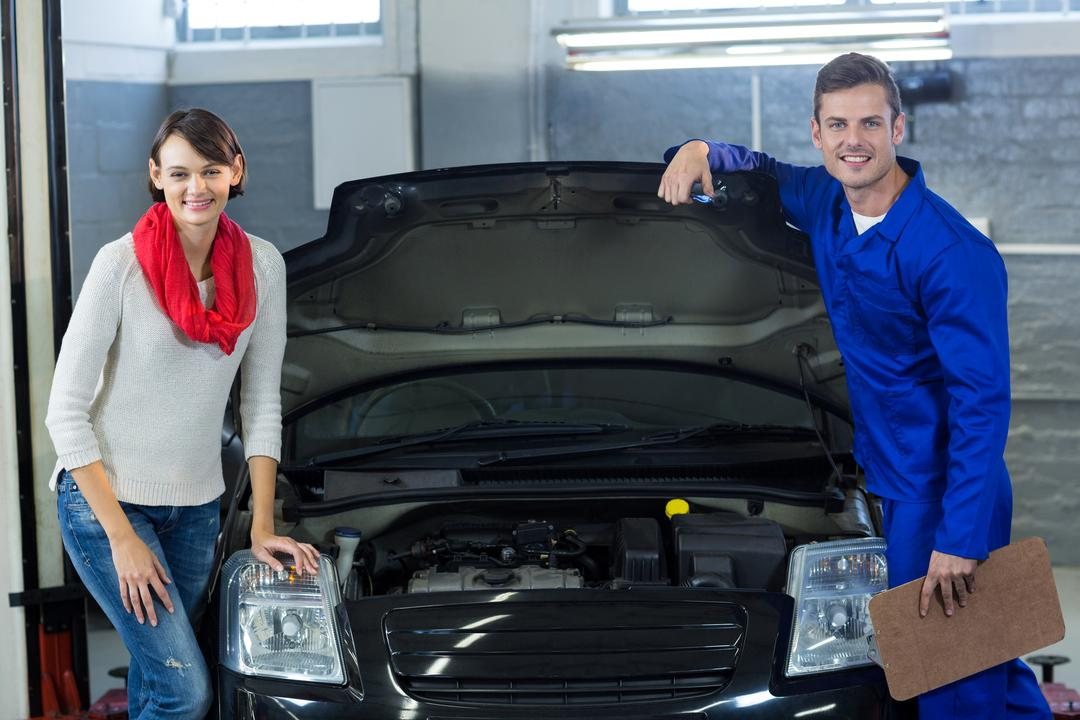 Mechanic and customer standing with car in repair garage