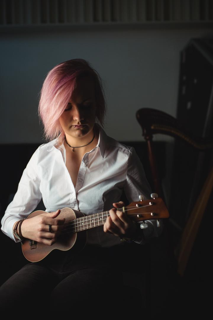 Woman playing a guitar in music school Free Stock Images from PikWizard