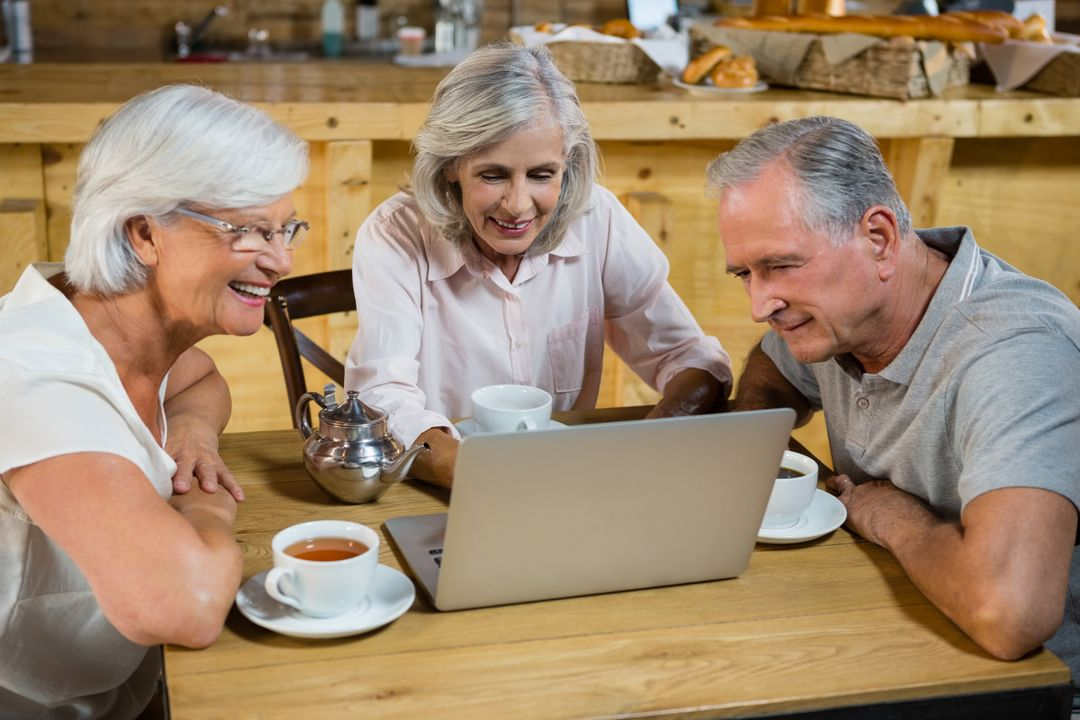 Group of senior friends using laptop in café Free Stock Images from PikWizard