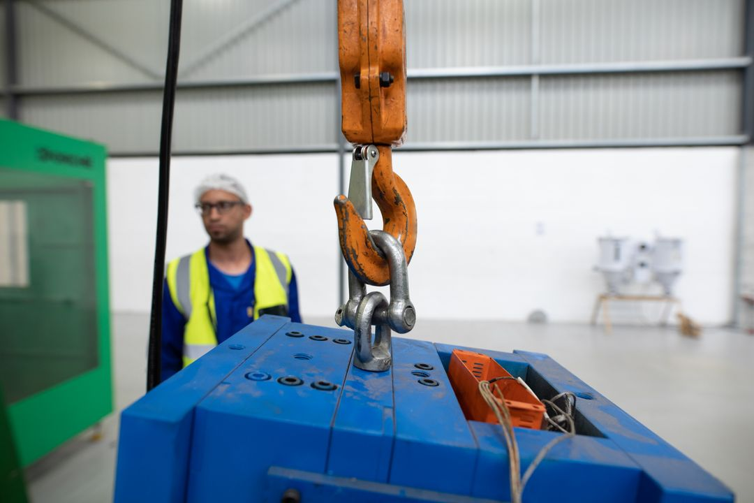 Front view of a mixed race male worker working in a factory warehouse, wearing a hair net, overalls and a high visibility vest, checking and operating a crane, lifting metal parts hanging from a crane hook, focus on the foreground Free Stock Images from PikWizard