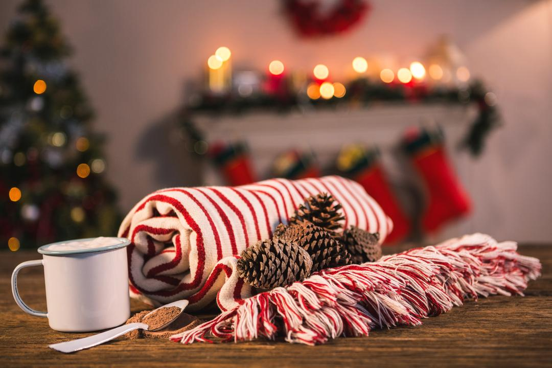 Rolled blanket with pine cone and coffee mug on wooden table