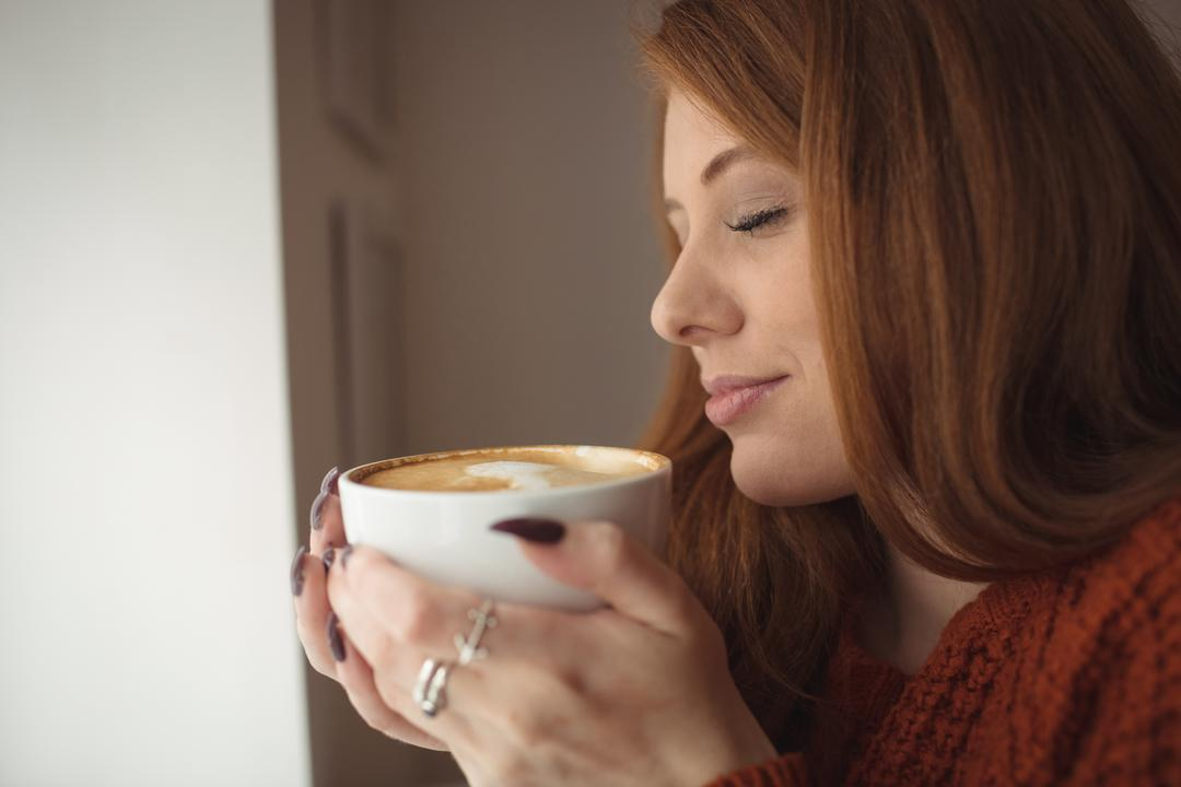 Close-up of beautiful woman holding coffee cup at window