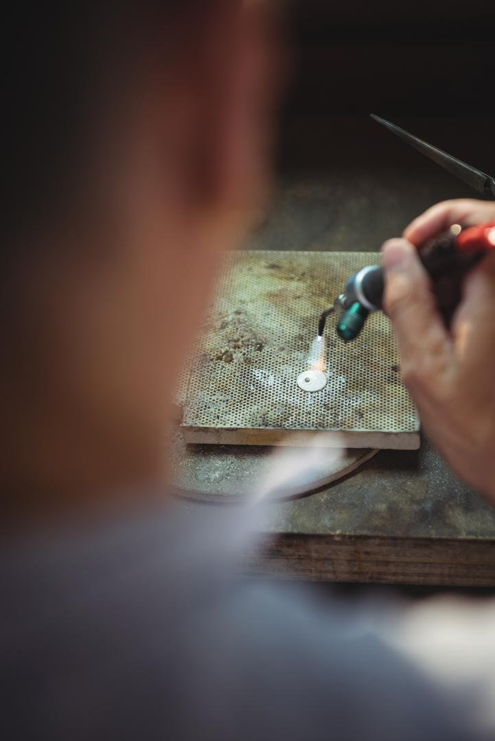 Close-up of craftswoman using blow torch in workshop