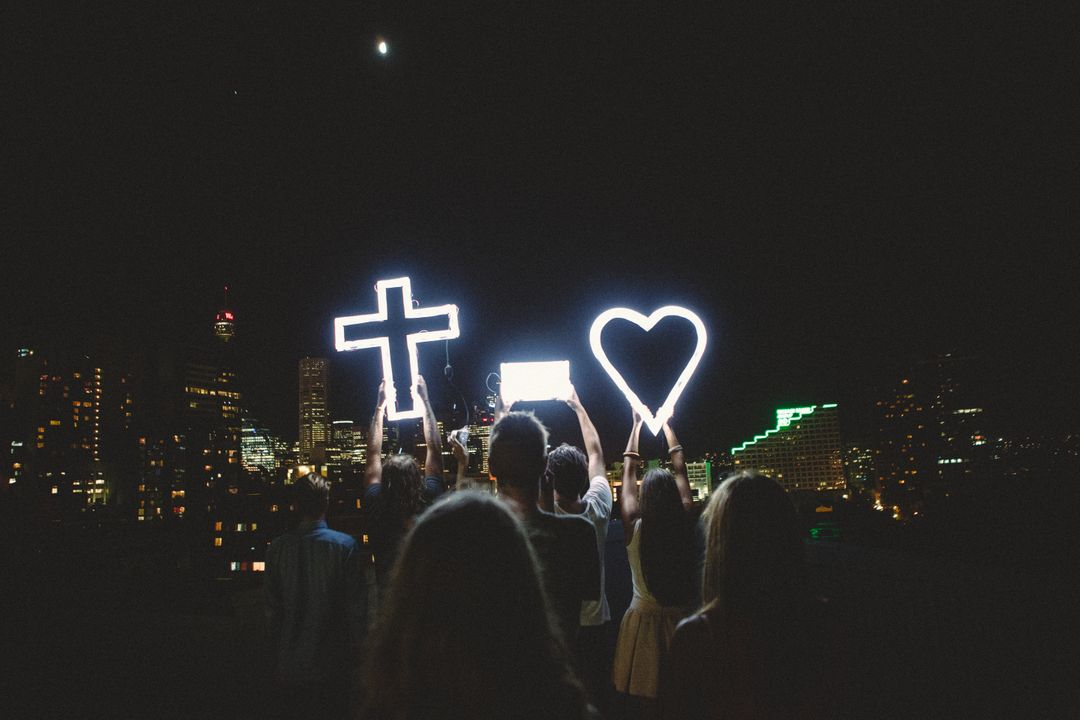 Man and Lady Raising Cross Heart Led Light Photo during Night Time