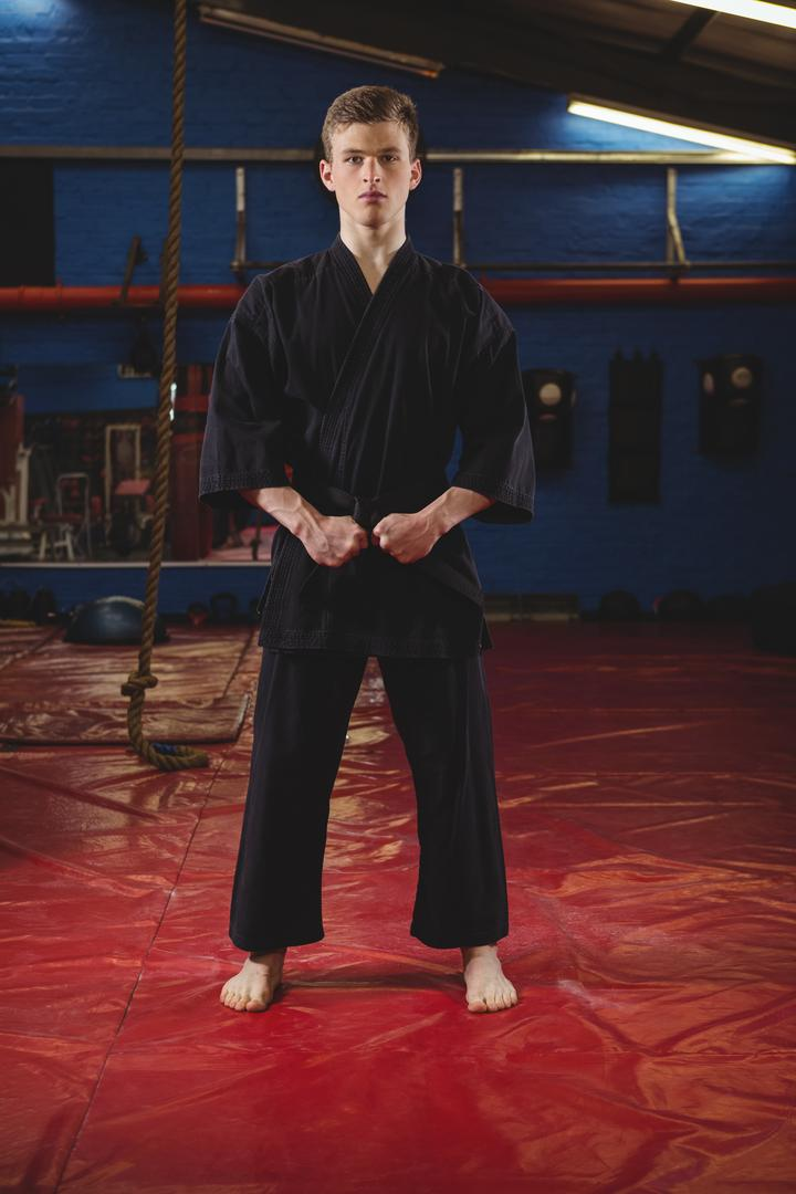 Portrait of karate player performing karate stance in fitness studio Free Stock Images from PikWizard