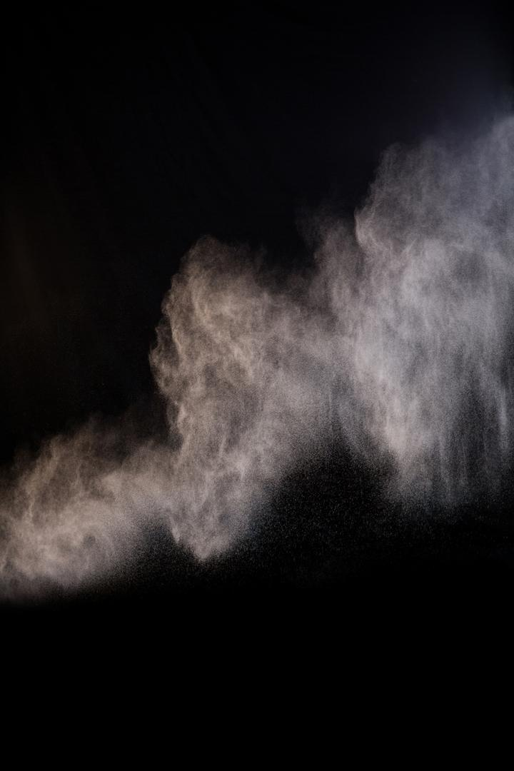 Splashing of dust powder on black background