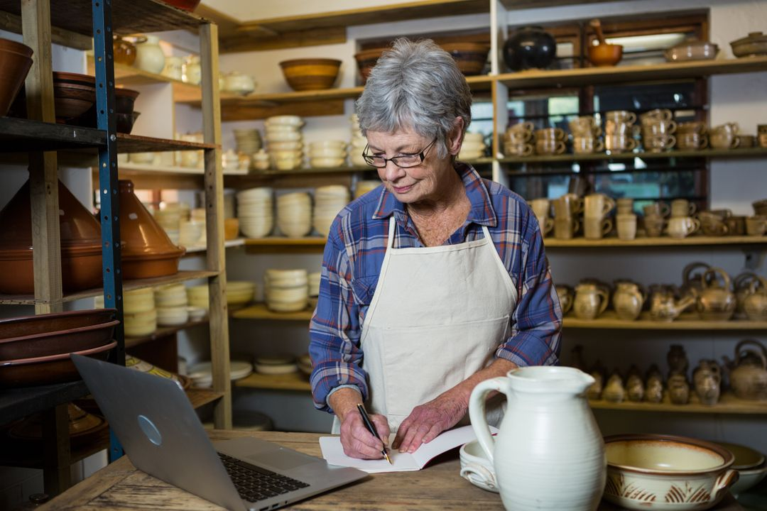 Female potter making note from laptop in pottery shop Free Stock Images from PikWizard