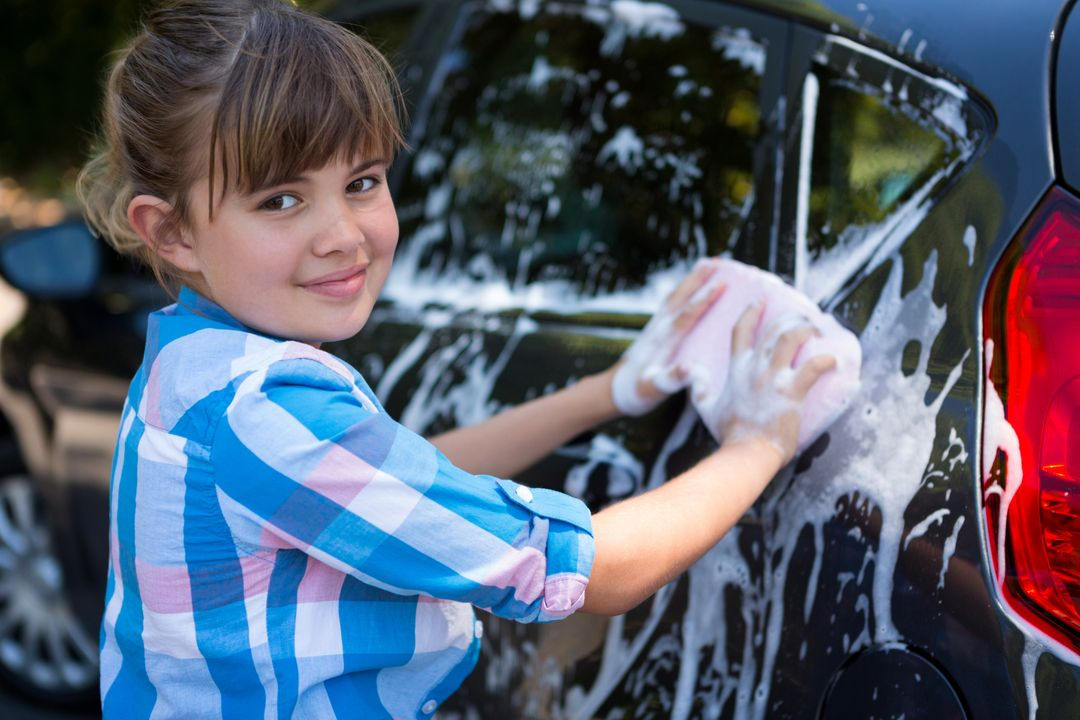 Portrait of teenage girl washing a car on a sunny day