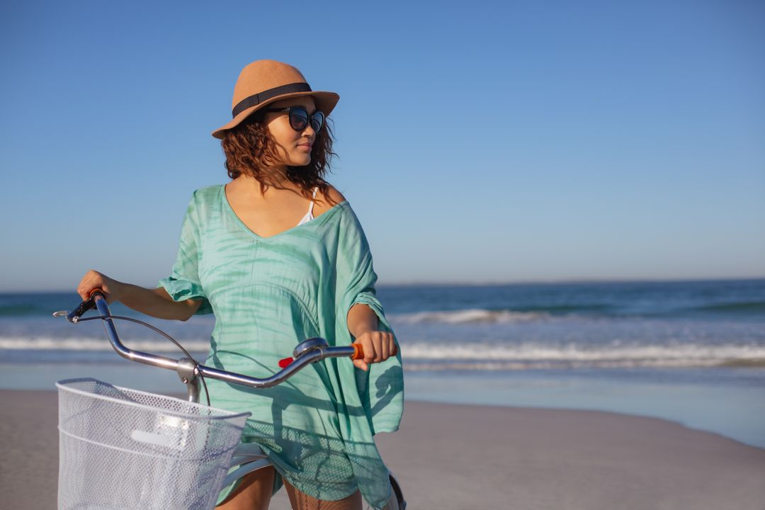 Front view of beautiful mixed race woman with bicycle looking away on beach in the sunshine
