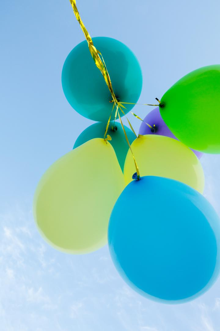 Bunch of pastel color balloons floating in the air against blue sky