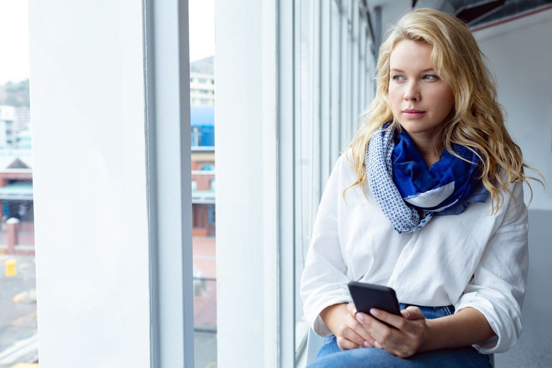 Front view of beautiful young Caucasian businesswoman looking away while using mobile phone near window in a modern office