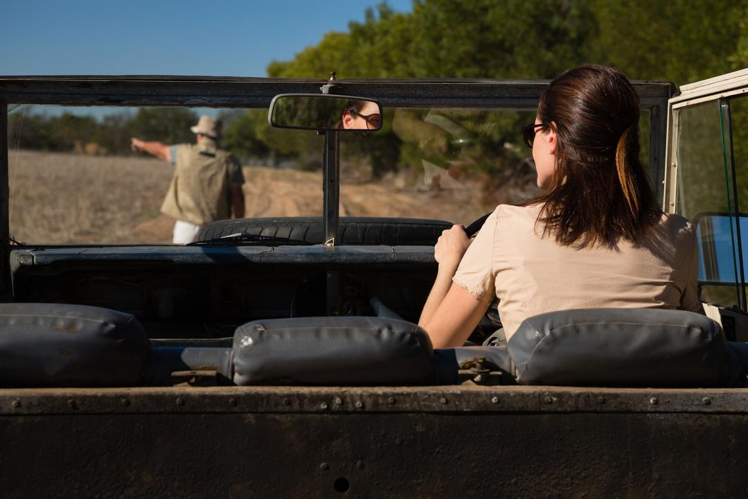 Rear view of man seen through windshield with woman driving off road vehicle on landscape