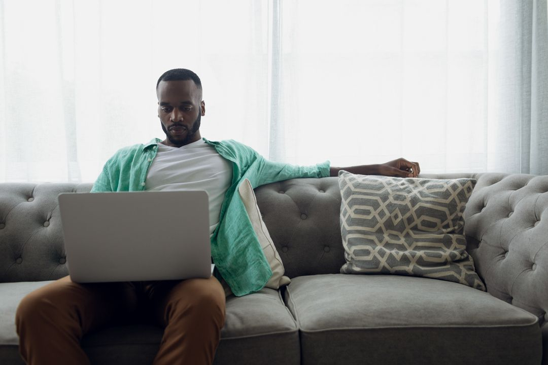 Digital composite of an African-American man sitting on a grey couch with white curtains inside a room while using a laptop