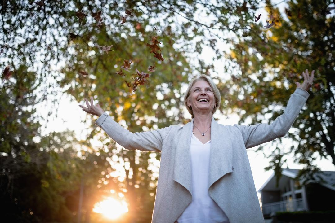 Smiling woman standing with arms outstretched on a sunny day
