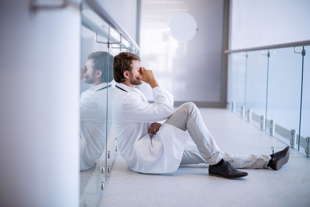 Tensed doctor sitting in corridor of hospital Free Stock Images from PikWizard