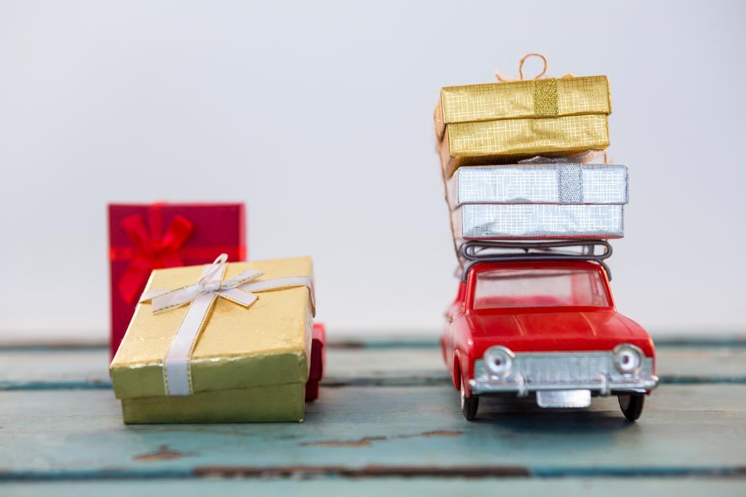 Toy car carrying christmas present on wooden plank during christmas time