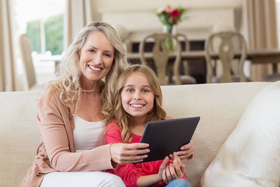 Portrait of mother and daughter using digital tablet at home Free Stock Images from PikWizard