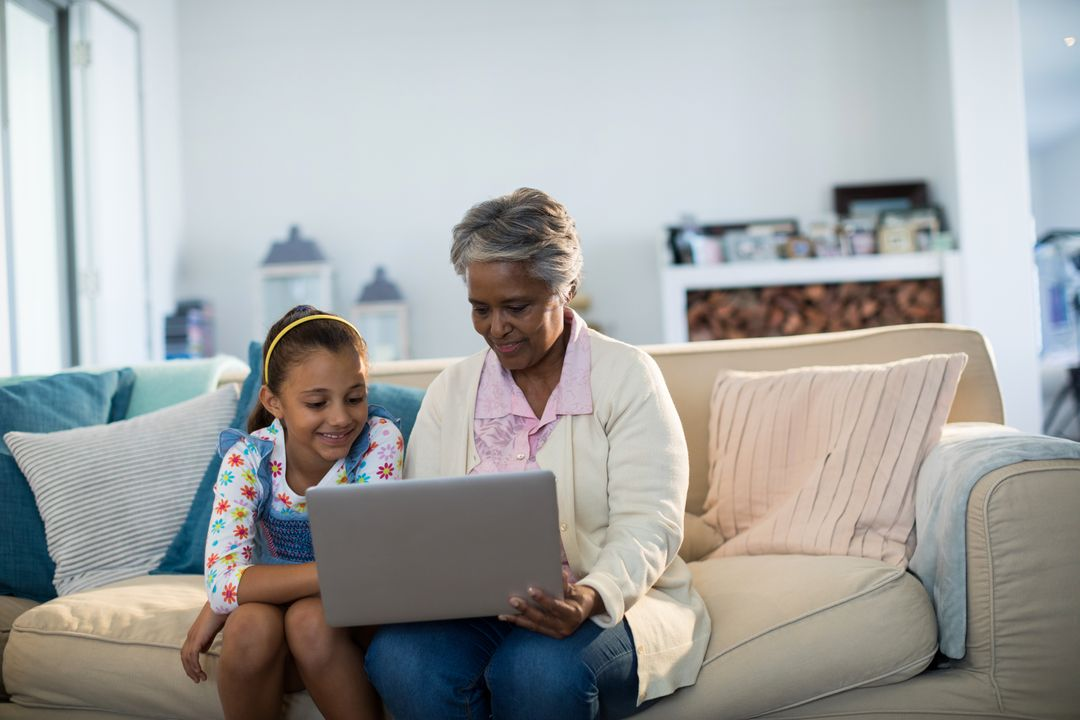 Grandmother and granddaughter using laptop in living room at home