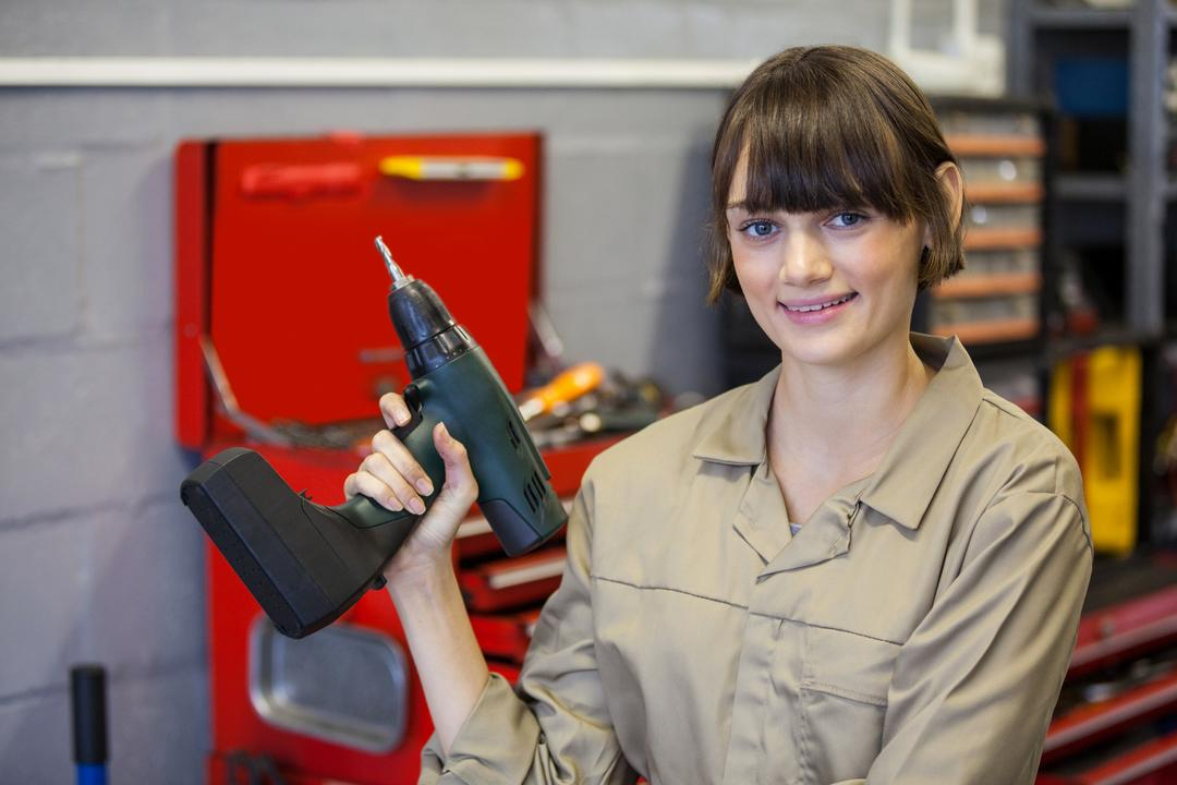 Female mechanic with pneumatic wrench at the repair garage