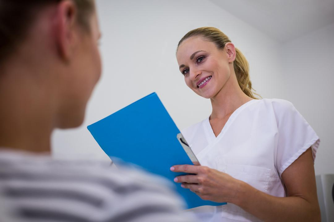 Smiling doctor holding medical reports at clinic Free Stock Images from PikWizard