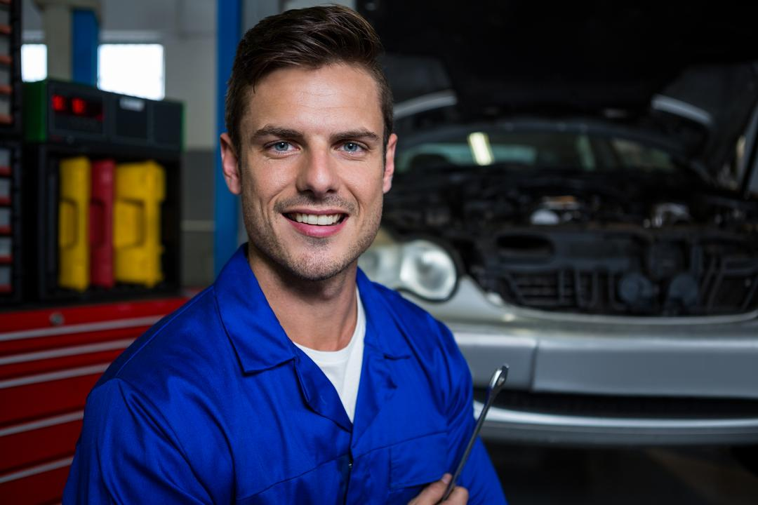 Portrait of happy mechanic holding spanner at repair garage