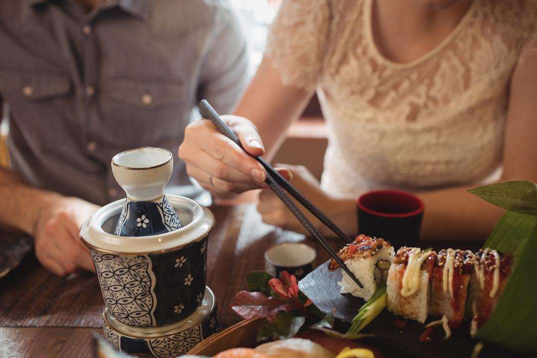 Mid section of couple having sushi in restaurant
