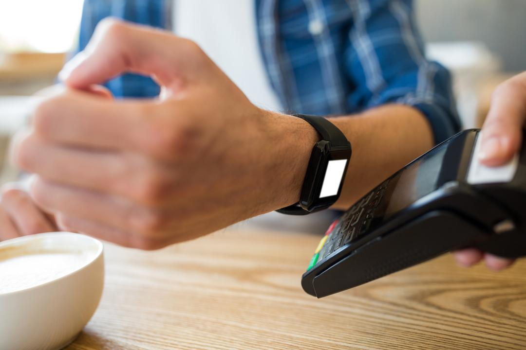 Man using smart watch for express pay at table Free Stock Images from PikWizard