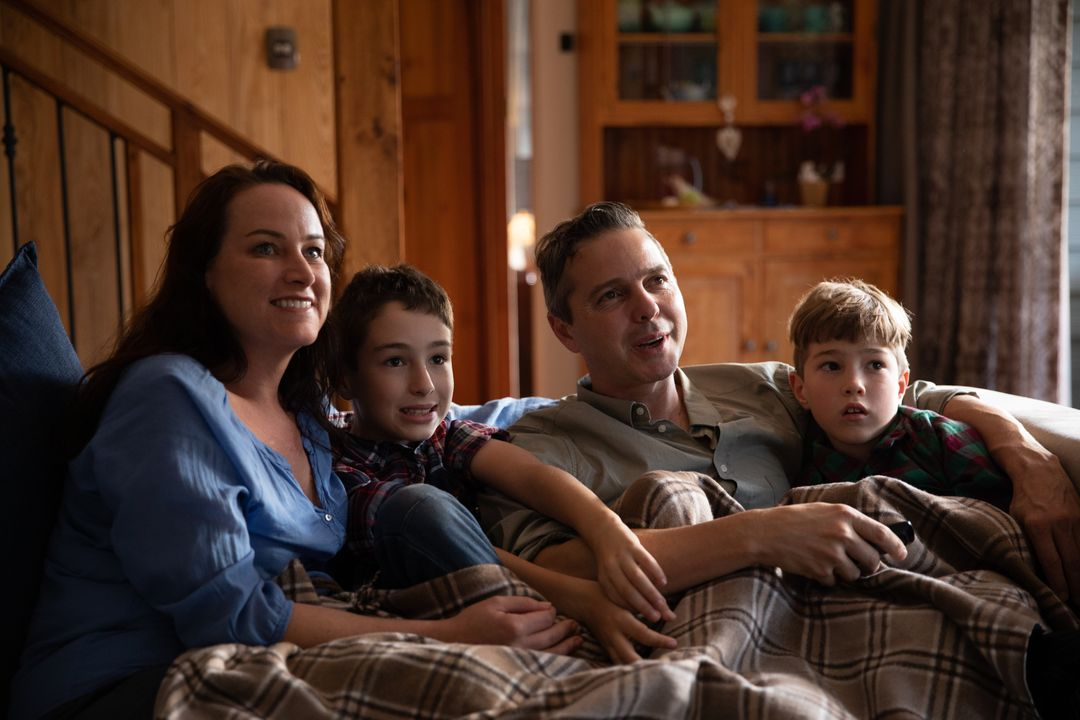 Front view of a couple with their two sons sitting together at home in their sitting room on a sofa, smiling and watching television.