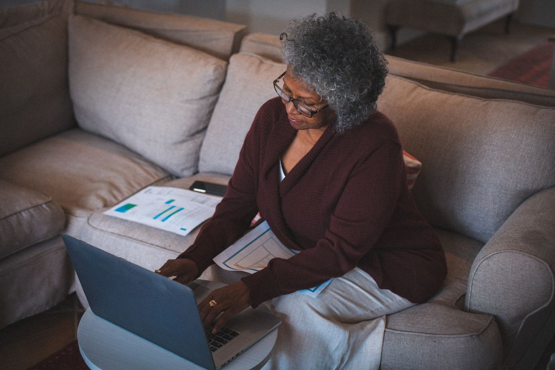 Woman wearing glasses typing on her laptop on her couch at night