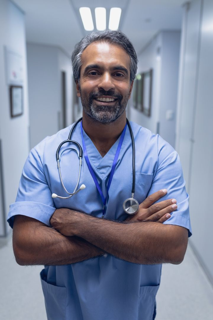 Portrait of male doctor standing with arms crossed in the corridor at hospital