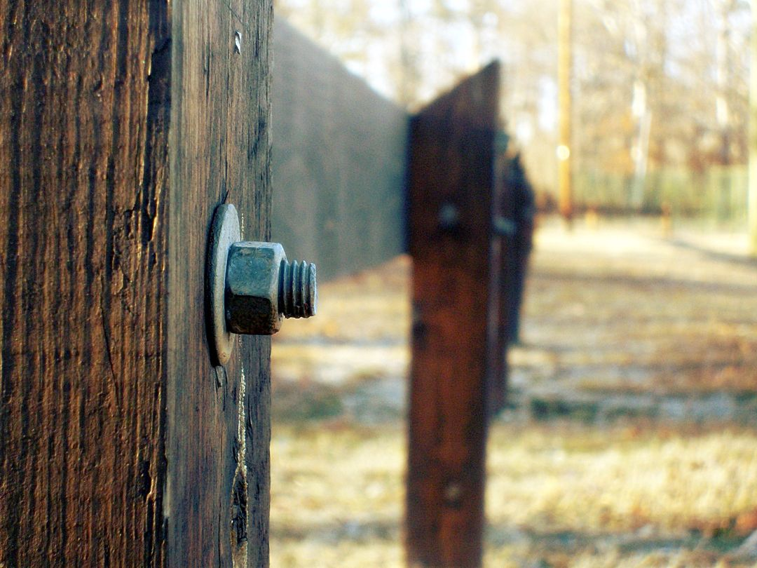 Selective Focus Photography of Grey Bolt Pierced in Brown Wooden Fence during Daytime