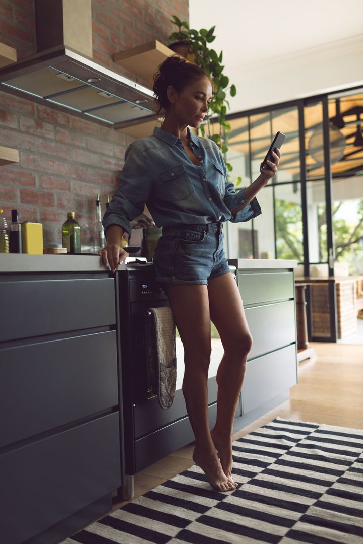 Beautiful woman using mobile phone in kitchen at comfortable home