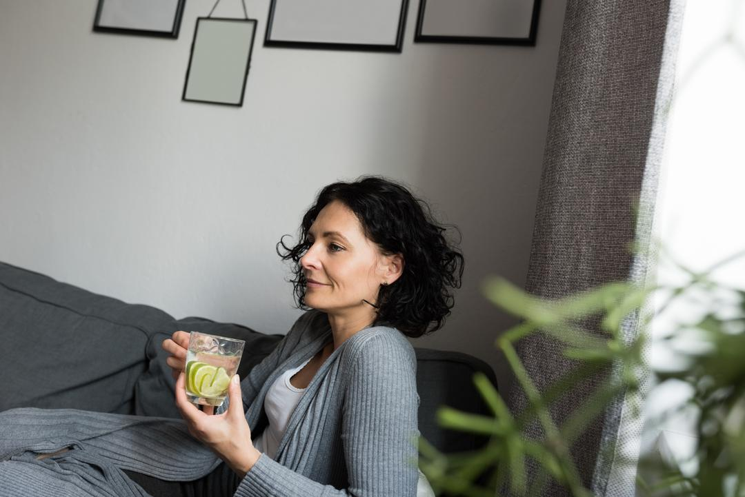 Woman holding a drink while sitting on the couch at home Free Stock Images from PikWizard
