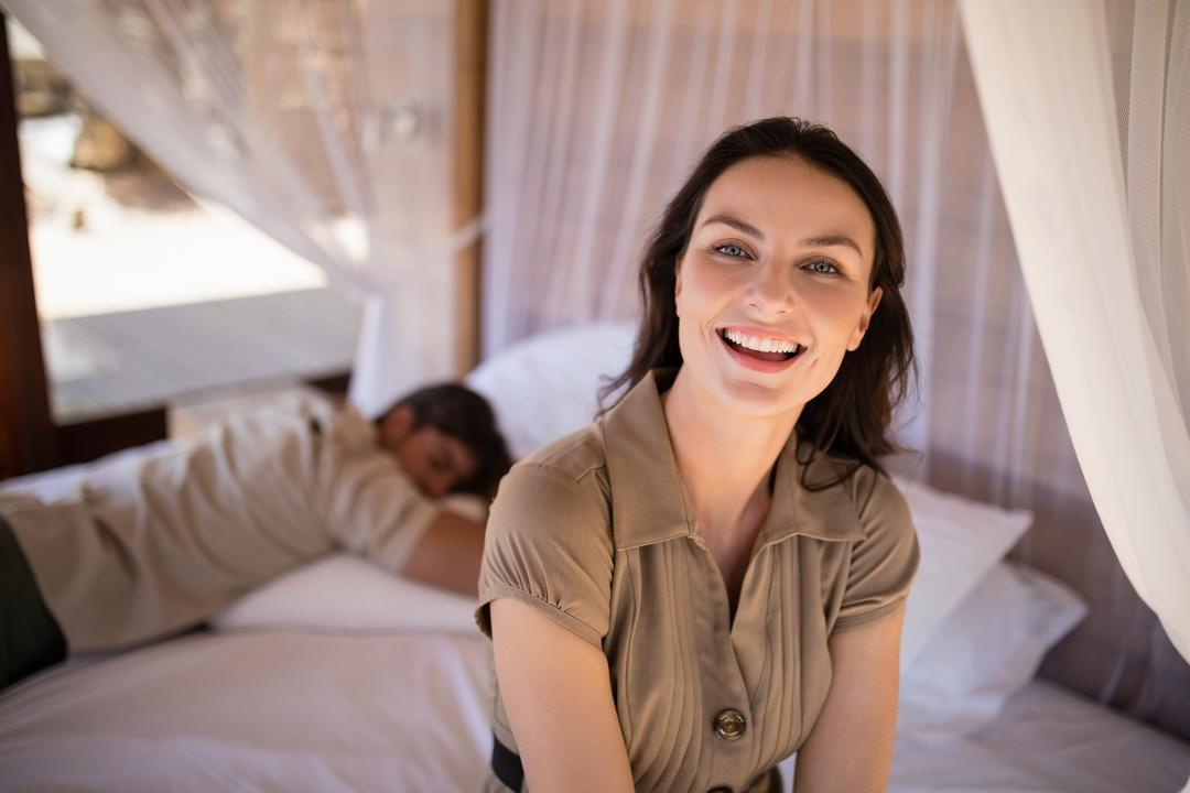Portrait of smiling woman sitting on canopy bed during safari vacation