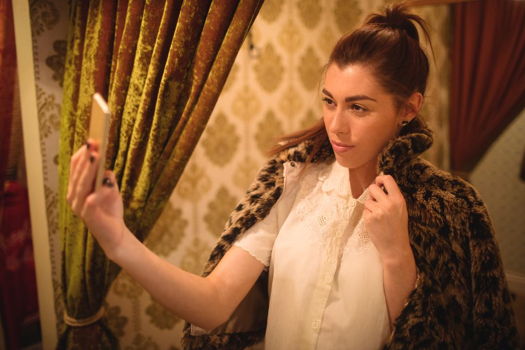 Woman taking selfie from mobile phone while trying a fur jacket at boutique store