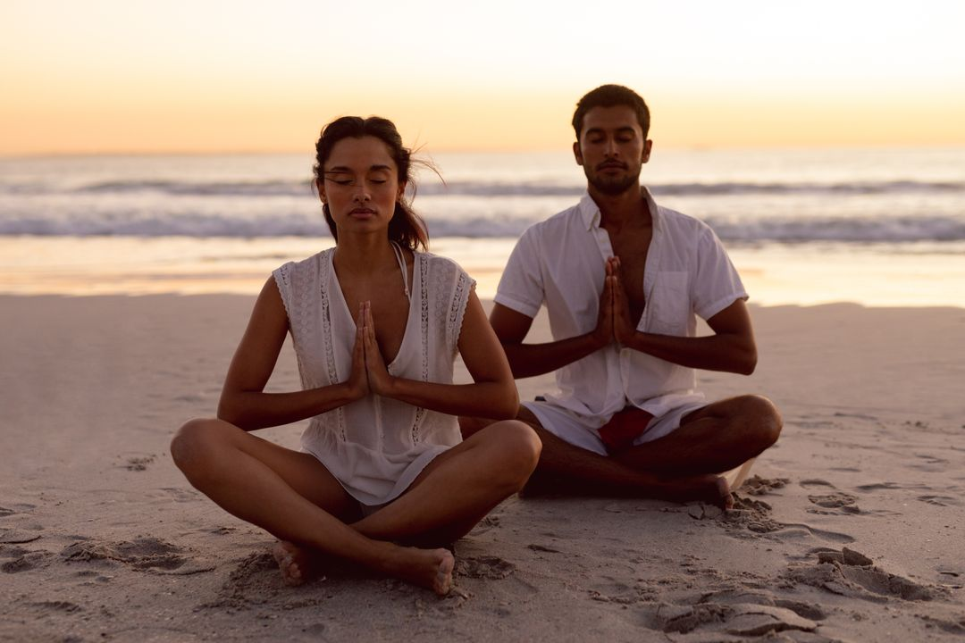 Couple performing yoga together on the beach during sunset