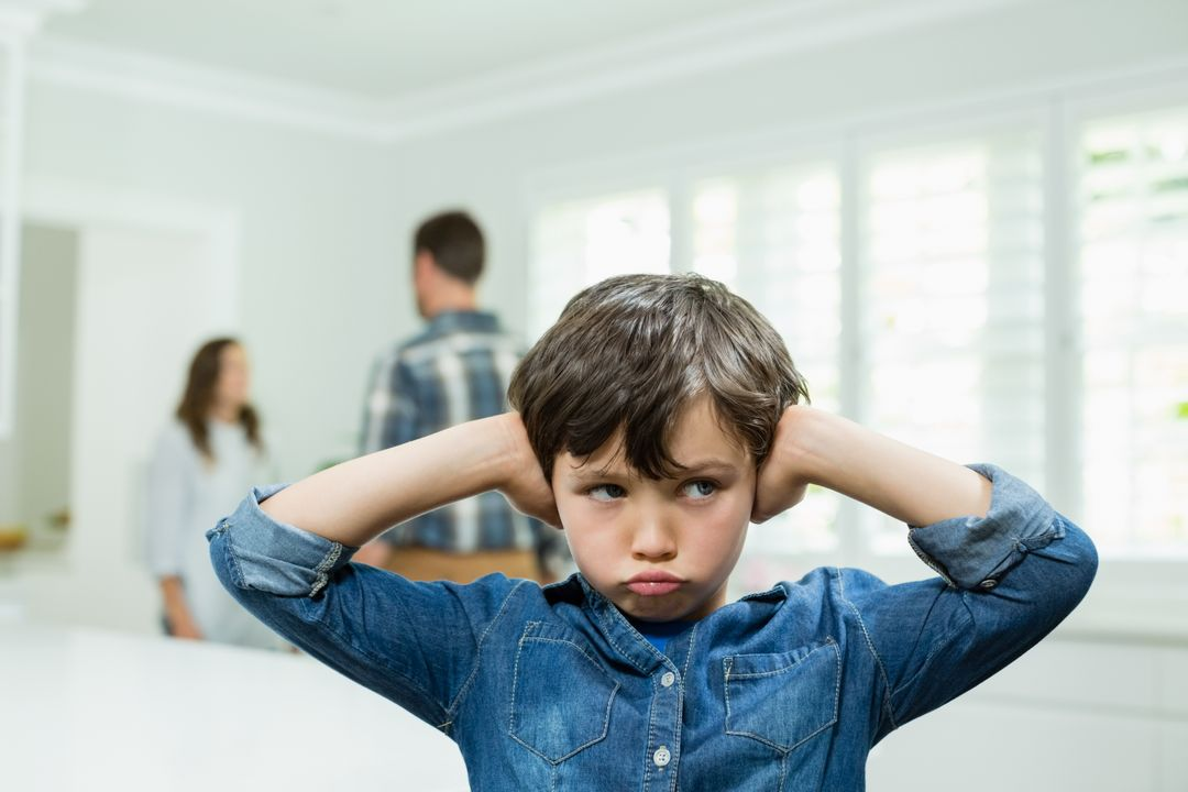 Boy covers his ears with his hands while parents arguing in background at home Free Stock Images from PikWizard