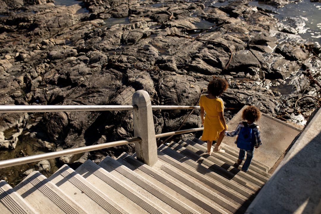 High angle rear view of a mixed race woman wearing a yellow dress and her son enjoying time together by the sea, holding hands and walking down stairs from a promenade to the beach on a sunny day Free Stock Images from PikWizard