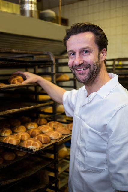 Smiling baker placing baked buns in shelf
