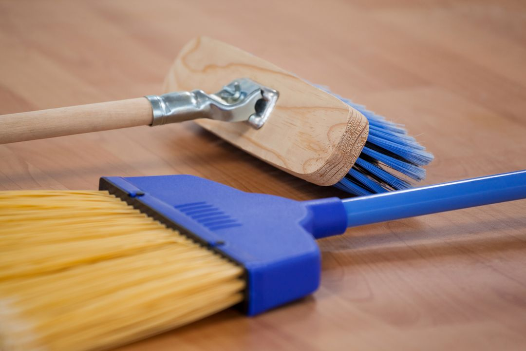 Close-up of two sweeping brooms on wooden floor Free Stock Images from PikWizard