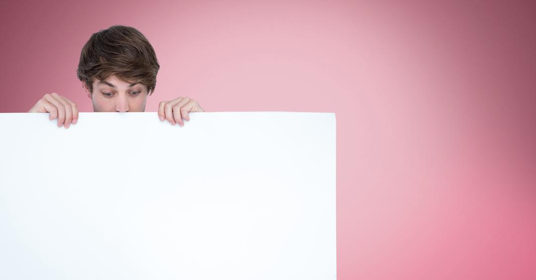 Digital composite of Surprised man looking at blank billboard while standing against pink background