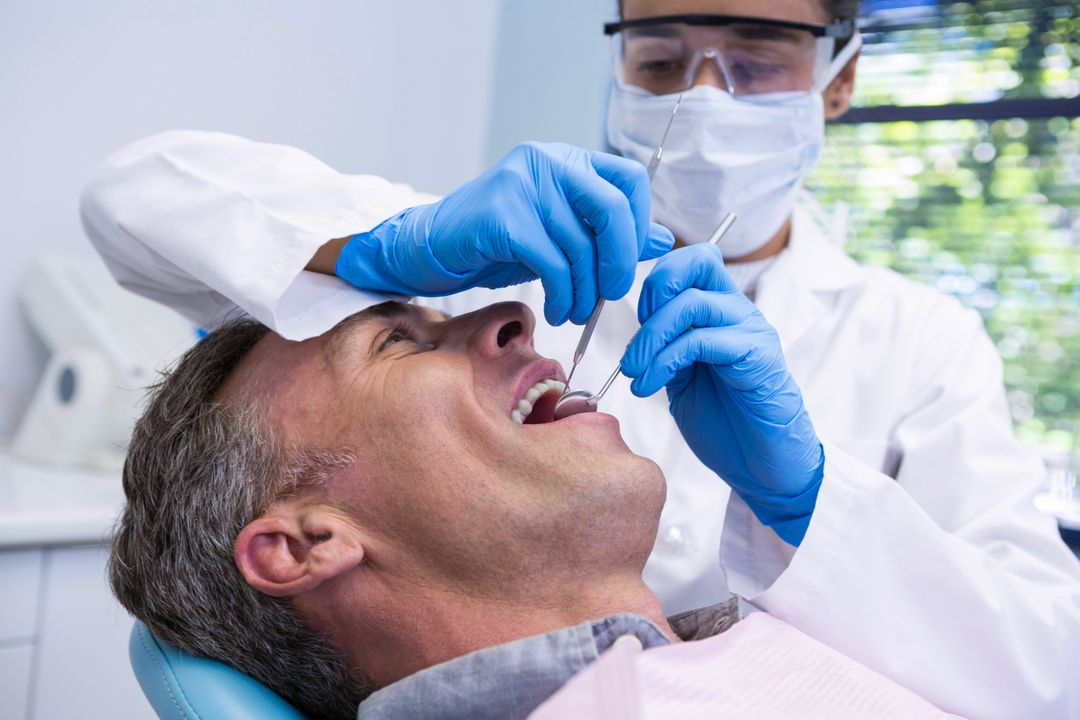Happy man receiving dental treatment by dentist at clinic Free Stock Images from PikWizard