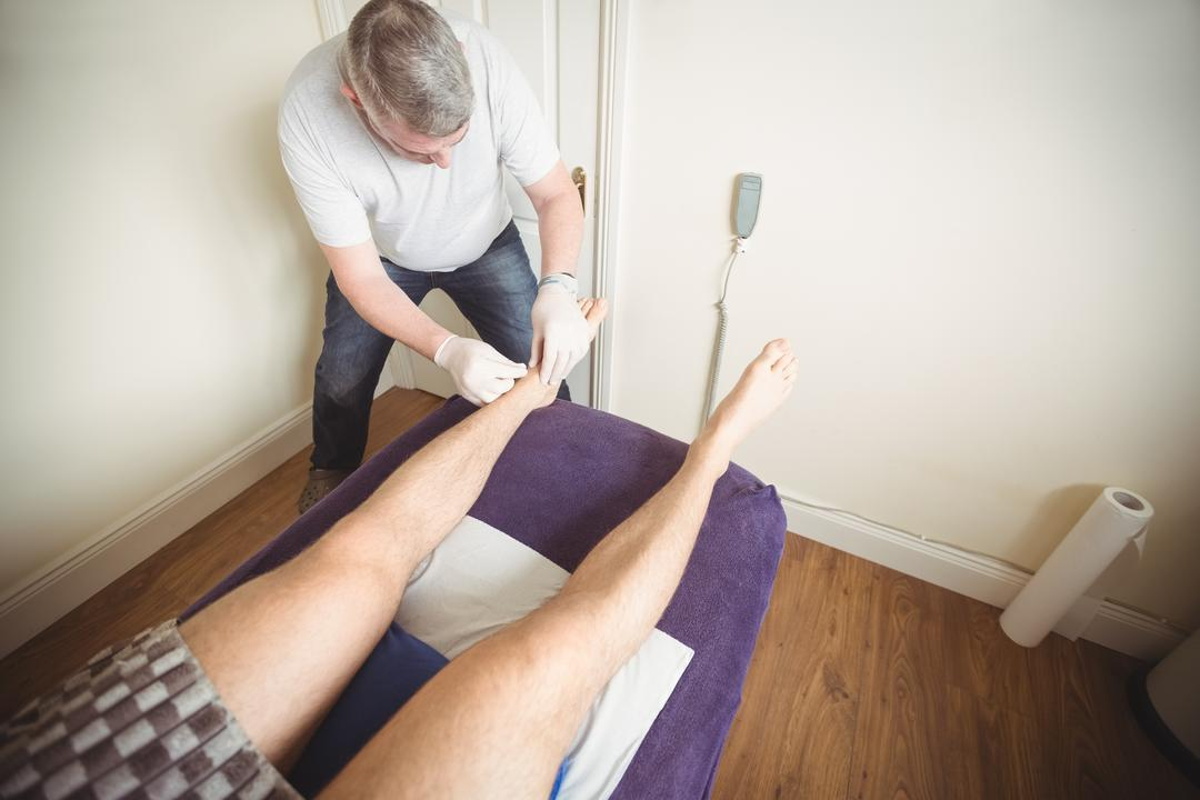 Physiotherapist performing dry needling on the leg of a patient in clinic Free Stock Images from PikWizard