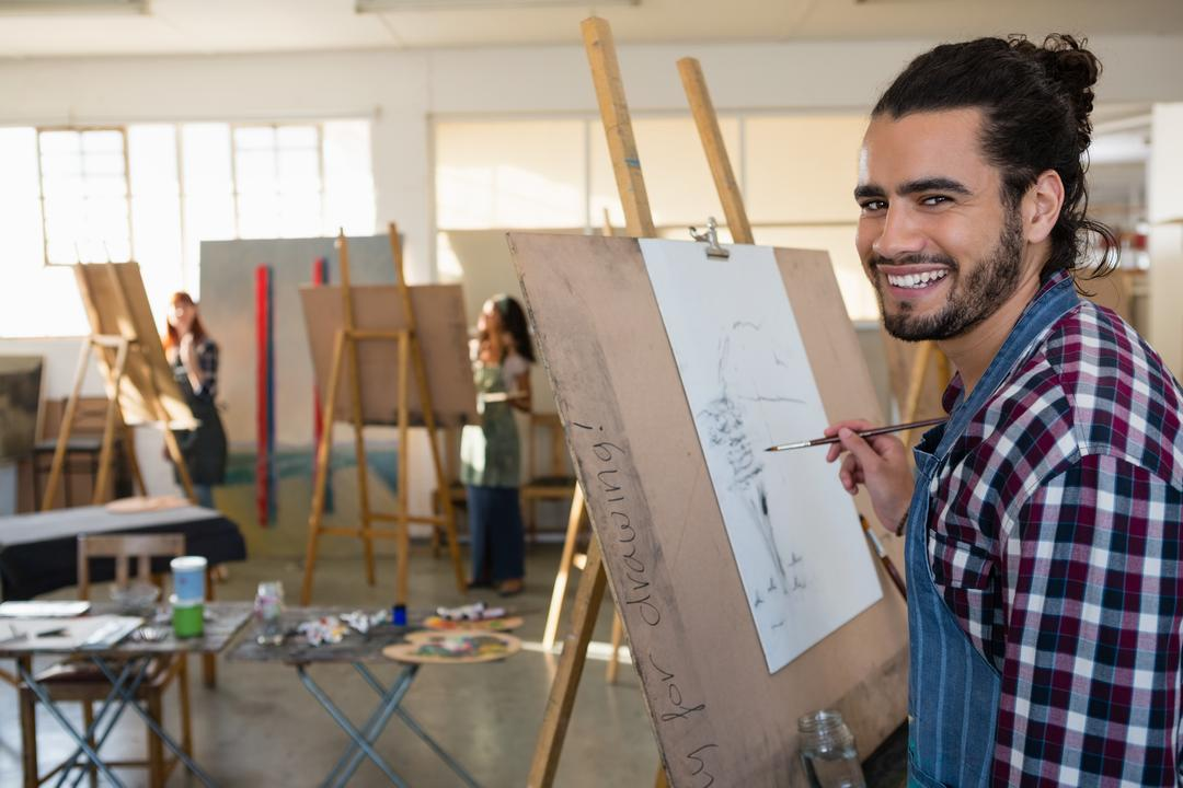 Portrait of smiling man painting on paper in art class Free Stock Images from PikWizard