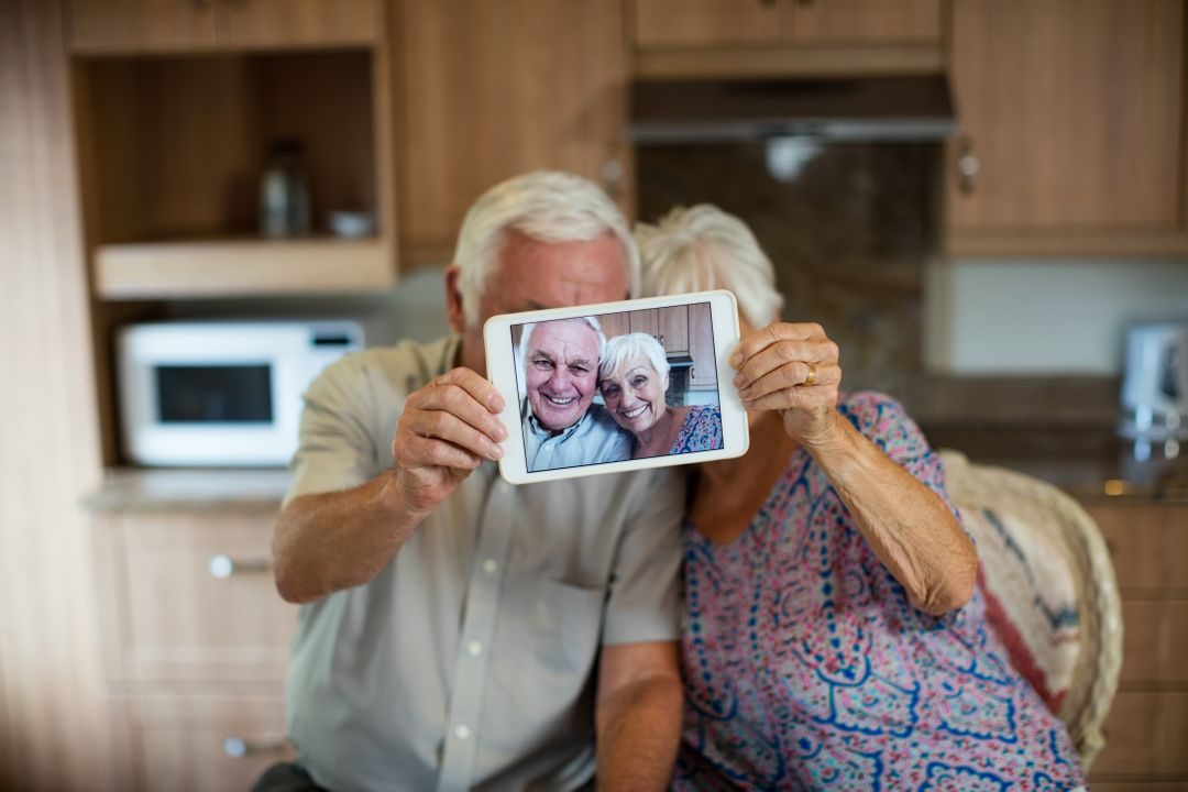 Senior couple taking selfie from digital tablet in kitchen at home Free Stock Images from PikWizard