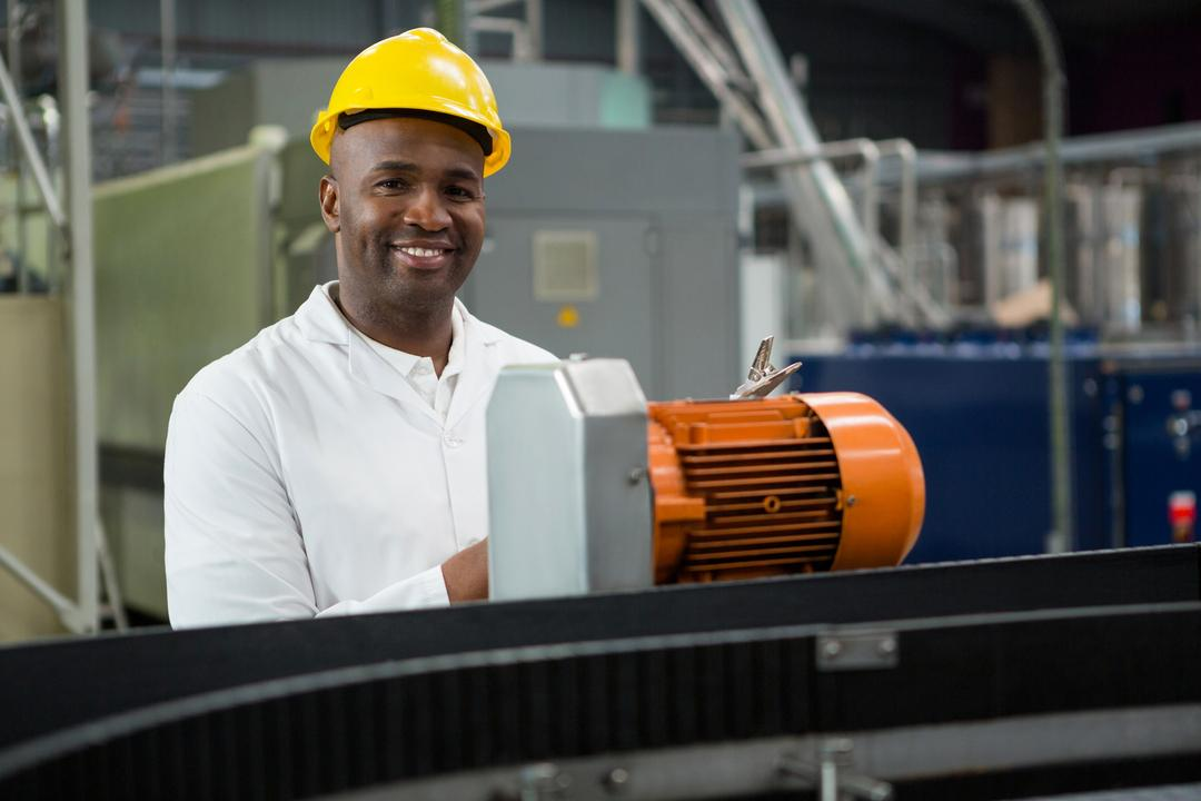 Portrait of smiling engineer inspecting machines at juice factory